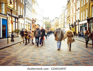 Shoppers walking on busy high street- motion blurred and defocused