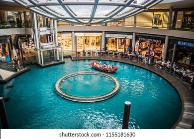 The Shoppes at Marina Bay Sands, Singapore / Singapore - June 9, 2018: A family is enjoying The Sampan ride at the Shoppes at the Marina Bay Sands