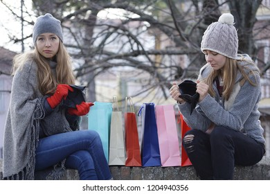 shopping addiction. two cute girls holding empty wallets after shopping too much. concept of careless consumerism, black friday sales and over spending