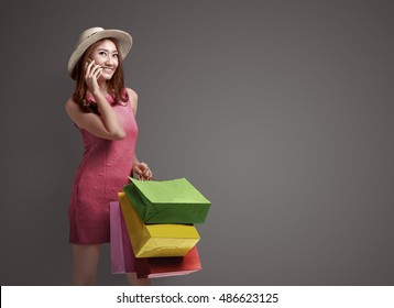 Shopping asian woman talking on the phone and holding bags on the gray background
