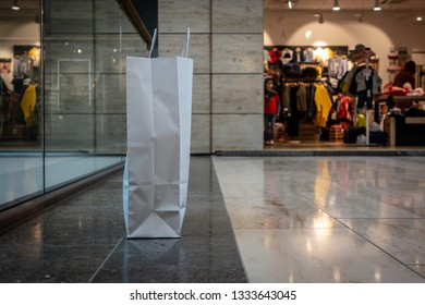 a shopping bag made of paper stands on the hallway of a shopping center