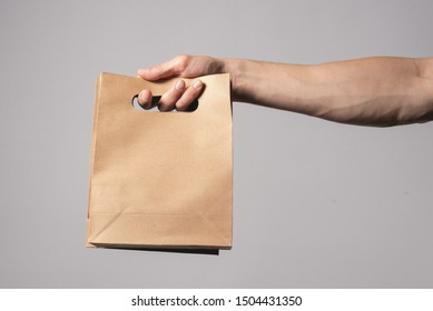 A shopping bag in a male hand isolated on gray background.