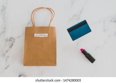 shopping bag on marble table top with lipstick and payment card, shot at shallow depth of field with soft muted tones