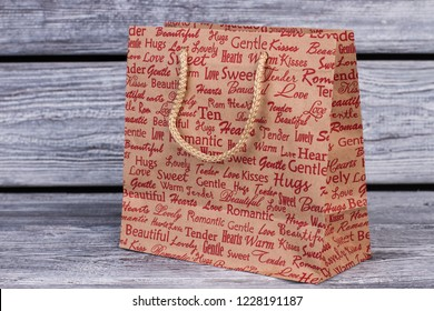 Shopping bag on wooden background. Brown paper gift bag with red printing. Valentine Day gift bag.