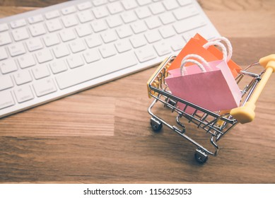 Shopping bag, supermarket cart with keyboard computer. Worldwide online shopping b2c ecommerce on internet website at home. Customer can buy product items and delivery service 24 hrs from online store
