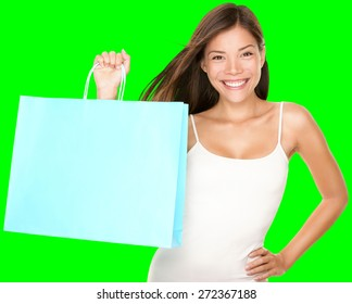 Shopping bag woman. Beautiful smiling happy woman holding showing blue shopping bag isolated cutout on green chroma key background. Fresh multiracial Asian Caucasian female model.
