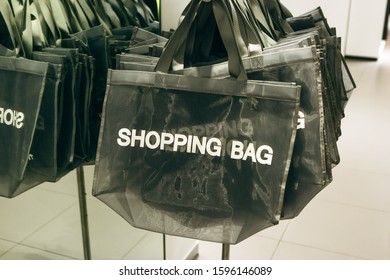 Shopping bags are hanging in a row inside the store for customers.