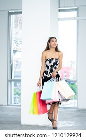Shopping bags portrait of a happy Asian pretty girl,Glamorous beautiful young woman in elegant fitting dress with alluring and takes off sunglasses with shopping bag,Seasonal sale,