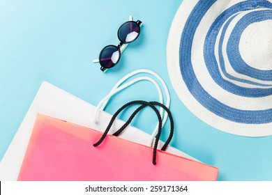 Shopping bags and sunglasses with hat on blue background