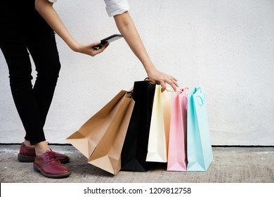 Shopping bags were picking up by woman crazy shopaholic hand,and hold mobile phone, at shopping mall.colorful paper shopping bags.
