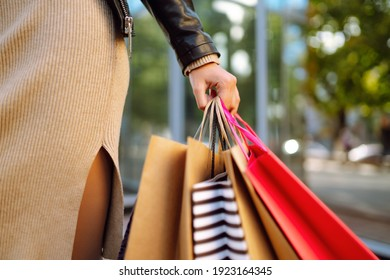 Shopping bags in the woman hands. Young woman after shopping on the city street. The joy of consumption, Purchases, black friday, discounts, sale concept.