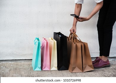 Shopping bags of women crazy shopaholic lady put on cement ground floor,and brown shopping bags are taking of by right hand,mobile phone was holding by left hand for shopping online.