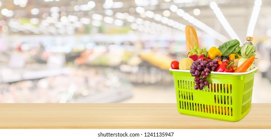 Shopping basket filled with fruits and vegetables on wood table with supermarket grocery store blurred defocused panorama background