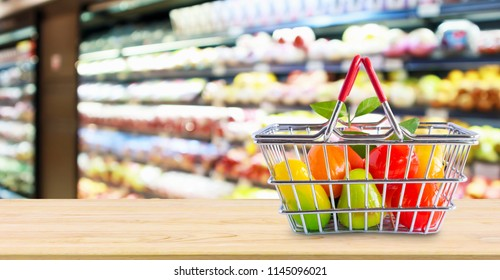 Shopping basket with fruit on wood table over grocery store supermarket blur background
