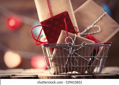 Shopping basket and gifts for Valentine's or Christmas with color bokeh on background
