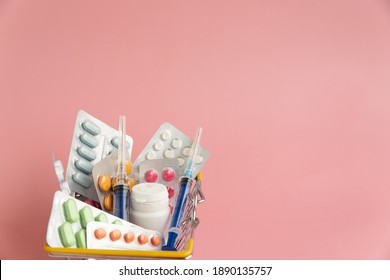 Shopping basket with medicinal pills and tablets closeup Isolated on light pink background