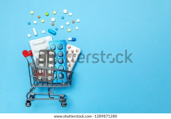 Shopping basket and pills in blisters. The concept of buying drugs online, delivery of medical devices. Copy space for text