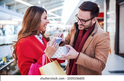 Shopping. Beautiful young couple enjoying in shopping, looking for presents in shopping mall. Consumerism, love, dating, lifestyle concept