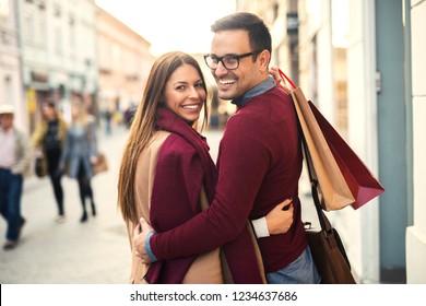 Shopping. Beautiful young couple enjoying in shopping, having fun together in the city.