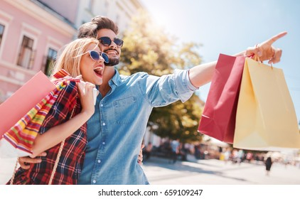 Shopping. Beautiful young couple enjoying in shopping, having fun in the city. Consumerism, love, dating, lifestyle concept
