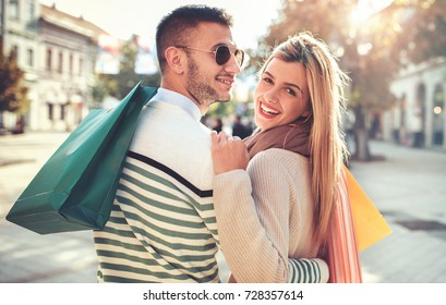 Shopping. Beautiful young couple enjoying in shopping, having fun together in the city. Consumerism, love, dating, lifestyle concept