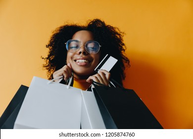 Shopping. Black friday. Afro American girl in eyeglasses is holding shopping bags and a credit card and smiling, on a yellow background