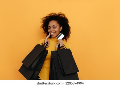 Shopping. Black friday. Afro American girl in yellow sweater is holding shopping bags and a credit card and smiling, on a yellow background
