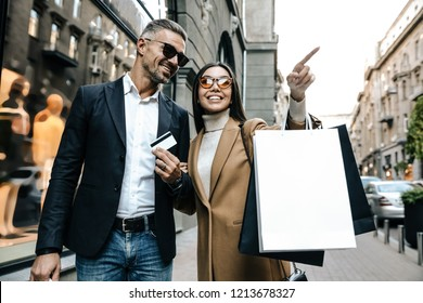 Shopping. Black Friday. Couple. Love. Man and woman with shopping bags and credit card are smiling while walking down the street. Girl is pointing