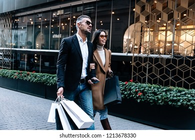 Shopping. Black Friday. Couple. Love. Man and woman with shopping bags are talking and smiling while walking down the street
