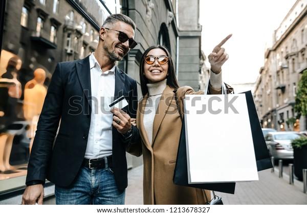 Einkaufen.Schwarzer Freitag. Paar. Liebe. Mann und Frau mit Einkaufstüten und Kreditkarte lächeln, während sie die Straße entlang gehen. Mädchen zeigt