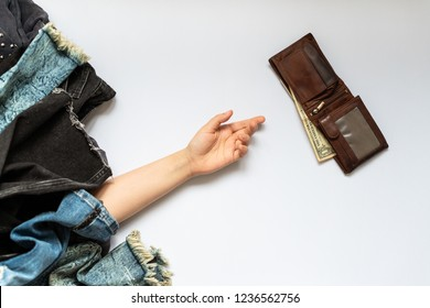 Shopping Black Friday or cyber monday concept. Shopaholic female hand reaches for the wallet with money. Uncontrollable shopping. Compulsive buying disorder or oniomania. Copy space.