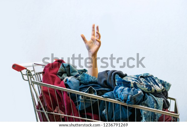 Shopping Black Friday or cyber monday concept. Shopaholic female  hand sticks out of the shopping cart full of clothes. Uncontrollable shopping - compulsive buying disorder or oniomania. Copy space.