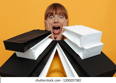 Shopping. Black friday. Emotion. Woman portrait. Girl is holding shopping bags, looking at camera with an open mouth, on a yellow background