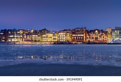 The shopping and business center Aker Brygge behind an icy sea. Oslo, Norway