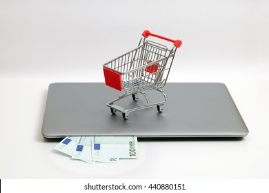 A shopping car is standing on notebook and three hundred euros