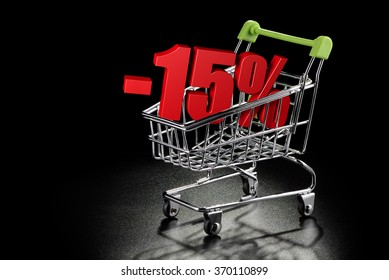 Shopping cart with 15 % percentage rate on a black textured background with copy-space