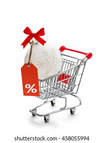 Shopping cart with big Christmas ball and percent, isolated