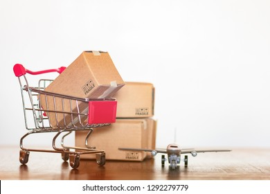 Shopping cart cartons and airplane. International shopping and Worldwide shipping concept