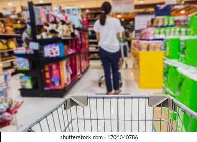 Shopping cart in checkout line at retail store with blurred woman in front during covid-19 social distancing.