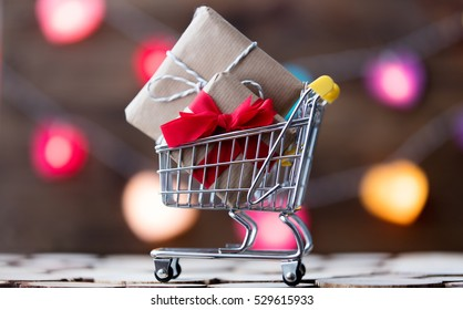 Shopping cart with Christmas and Valentine's gifts on color bokeh background