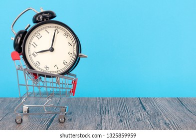 Shopping cart and classic alarm clock on wooden surface. Sale time buy mall market shop consumer concept. Selective focus.