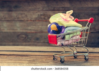 Shopping cart with clothing and baby pacifiers on the old wood background. Toned image.