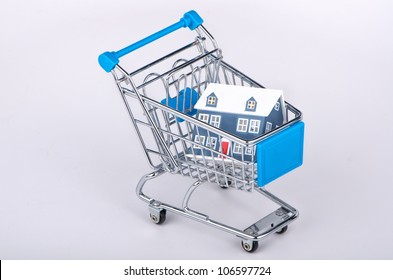 Shopping cart containing house - isolated on white background