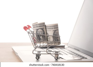 Shopping cart with dollar money on computer.