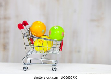 Shopping cart with Easter eggs on a wooden background.  Easter greeting card.Easter sale.