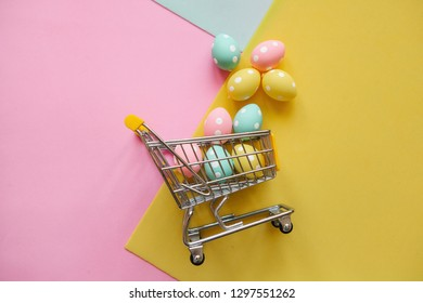 Shopping Cart with eggs on a multi-colored background. The concept of a festive Easter sale in a minimal style.