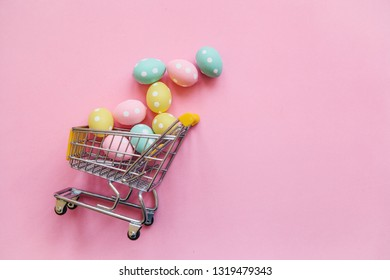 Shopping Cart with eggs on a pink background. The concept of a festive Easter sale in a minimal style.