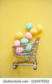 Shopping Cart with eggs on a yellow background. The concept of a festive Easter sale in a minimal style.
