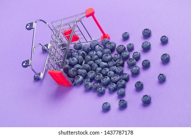 Shopping cart fell down and dropped blueberries on purple background
