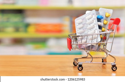 Shopping cart filled with blister packs of medicine on pharmacy drugstore shelves background.Online medical concept.